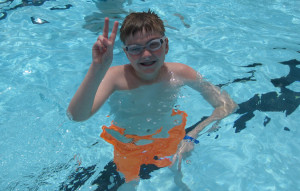 A camper having fun in the nice cold pool.