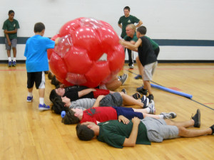 Campers working with an inflatable ball activity.